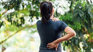woman facing away grabbing shoulder and back