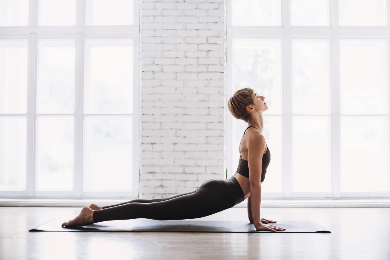 Young woman practicing yoga at class