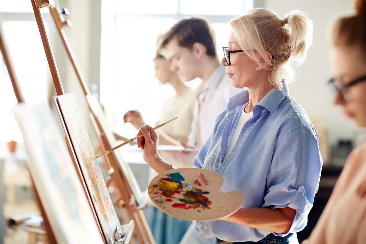Blonde mature woman painting picture on easel with mixed oil colors between her students
